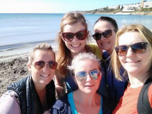 5 women close up with beach behind