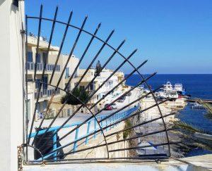 houses by a sea seen through a railing